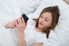 Girl With Mobile Phone In Bedroom Stock Photo