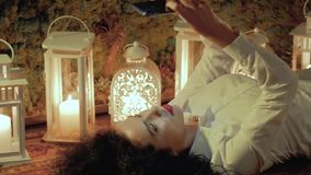 Woman uses smartphone on the floor. Girl with a mobile phone on the floor. Young curly woman in white with beautiful red lips is lying on the carpet, against the stock footage