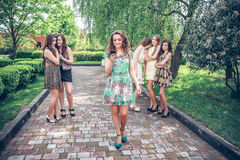 Girl with the mobile phone and group of envying girls Royalty Free Stock Photo