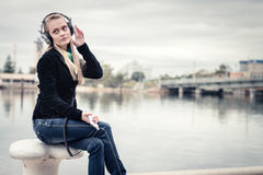 Girl with mobile phone and headphones Royalty Free Stock Photo
