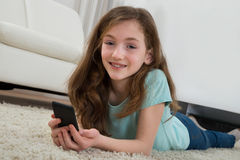 Girl With Mobile Phone In Living Room Stock Images