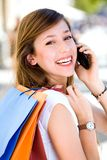 Girl with mobile phone and shopping bags Royalty Free Stock Images
