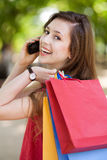 Girl with mobile phone and shopping bags Stock Images