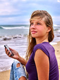 Girl with mobile phone sitting on sand near sea Royalty Free Stock Photography