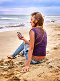 Girl with mobile phone sitting on sand near sea. Royalty Free Stock Photo