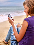 Girl with mobile phone sitting on sand near sea Royalty Free Stock Photo