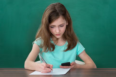 Girl With Mobile Phone Writing On Paper Stock Photo