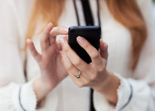 Girl and mobilephone. Young beautiful woman writes an SMS to your mobile phone Royalty Free Stock Image