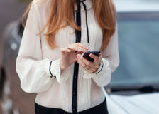 Girl and mobilephone. Young beautiful woman writes an SMS to your mobile phone Stock Photos