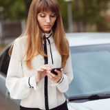 Girl and mobilephone. Young beautiful woman writes an SMS to your mobile phone Stock Photo