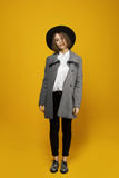 Girl model costs on a yellow background with a hat and coat. Girl in a coat, hat and silver shoes standing on zhetom background Royalty Free Stock Photography