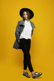 Girl model costs on a yellow background with a hat and coat. Girl in a coat, hat and silver shoes steps on yellow background Royalty Free Stock Images