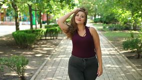 Portrait of a fat girl with long hair in the Park. Girl model overweight with long flowing hair posing in a Sunny summer city Park. Fat young teen girl in the stock video