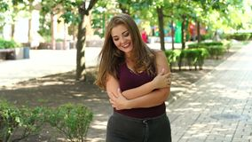 Girl model overweight with long flowing hair posing in a Sunny summer city Park. Fat young teen girl in the Park. Slow motion stock video footage