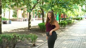 Girl model overweight posing in a Sunny summer city Park. Slow motion. Girl model overweight posing in a Sunny summer city Park. Fat young teen girl in the Park stock footage