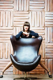 Girl posing for a leather armchair. Royalty Free Stock Images