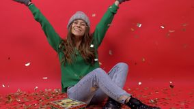 Girl model posing on a red background at the camera, under flying confetti. Girl model posing on a red background at the camera, under the flying golden confetti stock video
