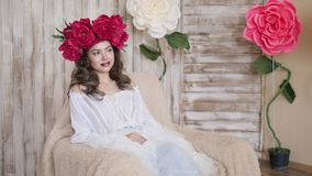 Girl model posing. a young woman in a wreath of scarlet peonies on her head, dark long curly hair descends on small Royalty Free Stock Photos