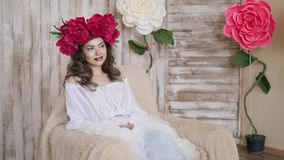Girl model posing. a young woman in a wreath of scarlet peonies on her head, dark long curly hair descends on small Stock Images