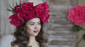 Girl model posing. a young woman in a wreath of scarlet peonies on her head, dark long curly hair descends on small Stock Photography