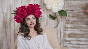 Girl model posing. a young woman in a wreath of scarlet peonies on her head, dark long curly hair descends on small Stock Photo