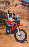 Girl model shows a new model Enduro bike. Stand with motorcycle innovations stock image