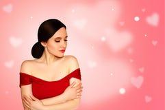 Girl modelo hermoso joven en vestido rojo en fondo rosa claro con los corazones día del ` s de la tarjeta del día de San Valentín Fotografía de archivo