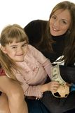Girl and moher saving money. Daughter and her mother are putting 1 dollar bill in the piggy bank royalty free stock images