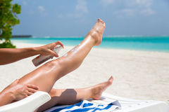 Girl moistures her legs with sun lotion Royalty Free Stock Photography