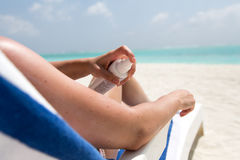 Girl moistures her legs with sun lotion Stock Image