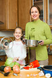 Girl and mom with casserole Stock Image