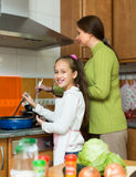 Girl and mom with casserole Royalty Free Stock Photos