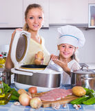 Girl and mom cooking with multicooker Stock Photos