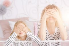 Girl and mom covering eyes. Little sweet girl and her mom covering their eyes royalty free stock photography