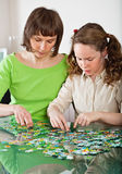 Girl and mom doing puzzle Royalty Free Stock Photos