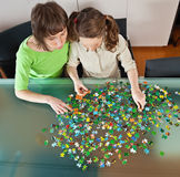 Girl and mom doing puzzle. Teenager girl and her mother doing a puzzle at home stock photos