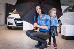 Girl and mom in exhibition hall for car Stock Image