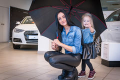 Girl and mom in exhibition hall for car Royalty Free Stock Photo