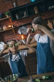 Girl and mom making faces while cooking royalty free stock image