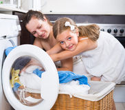 Girl and mom near washing machine. Cute little girl helping mom to load washing machine at home Stock Image