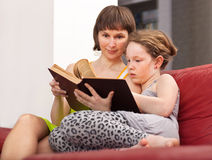 Girl and mom reading book. Teenager girl and her mother sitting on sofa and reading book together Stock Images