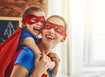 Girl and mom in Superhero costume. Mother and her child playing together. Girl and mom in Superhero costume. Mum and kid having fun, smiling and hugging. Family Stock Photo