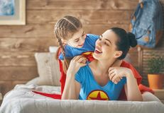Girl and mom in Superhero costume Stock Images