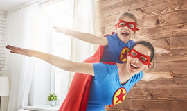 Girl and mom in Superhero costumes. Mother and her child playing together. Girl and mom in Superhero costume. Mum and kid having fun, smiling and hugging. Family Stock Images