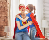 Girl and mom in Superhero costumes. Mother and her child playing together. Girl and mom in Superhero costume. Mum and kid having fun, smiling and hugging. Family Royalty Free Stock Image