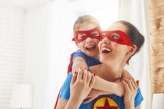 Girl and mom in Superhero costumes. Mother and her child playing together. Girl and mom in Superhero costume. Mum and kid having fun, smiling and hugging. Family Royalty Free Stock Photography