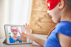 Girl and mom in Superhero costumes. Mother and her child playing together. Girl and mom in Superhero costumes. Mum and kid talking by using video link, having Stock Photo