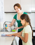 Girl and mom tidy kitchen Royalty Free Stock Photos