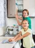 Girl and mom tidy kitchen up Stock Images