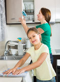 Girl and mom tidy kitchen up. Portrait of smiling girl and european mom tidy kitchen up Royalty Free Stock Photos